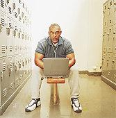 Coach sitting in locker room using laptop, portrait