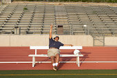 Coach sitting on bench on sidelines, holding one finger in air