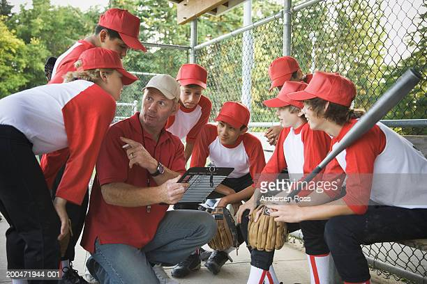 Coach talking to baseball players (9-14) in dugout
