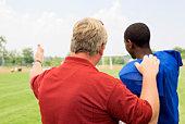 Coach talking to boy in football gear
