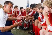 Coach talking to boys soccer team