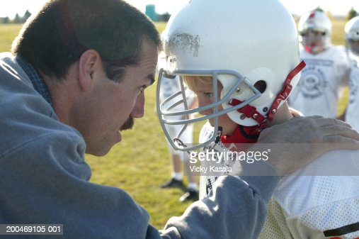 Coach talking to football player (10-12) on sideline, side view : Stock Photo