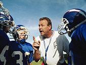 Coach talking to pee wee football team