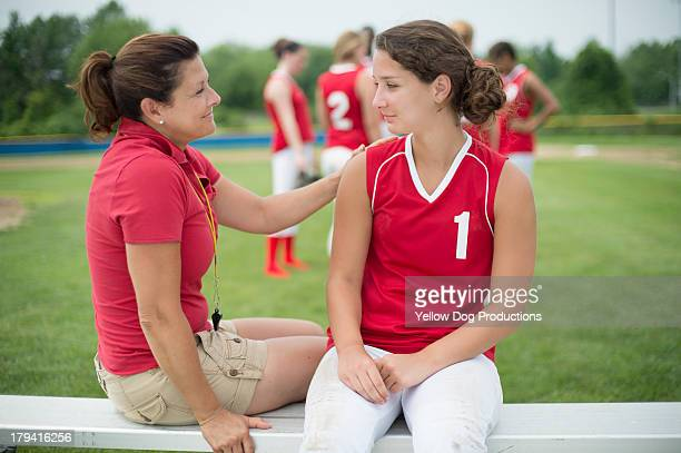Coach Talking to Softball Player sitting on bench