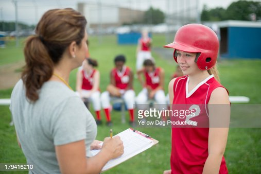 Coach Talking to Softball Player, teammates behind : Stock Photo