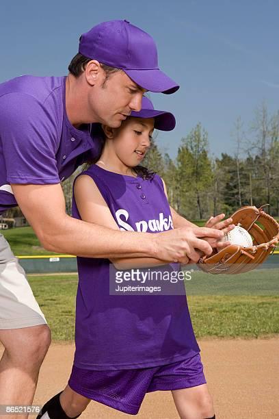 Coach teaching little league player
