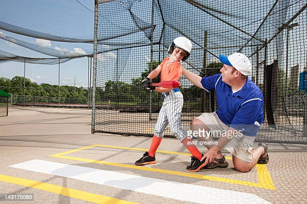Coach Teaching Youth League Baseball in Cage