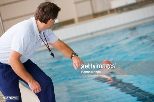 Coach timing swimmer in pool : Stock Photo