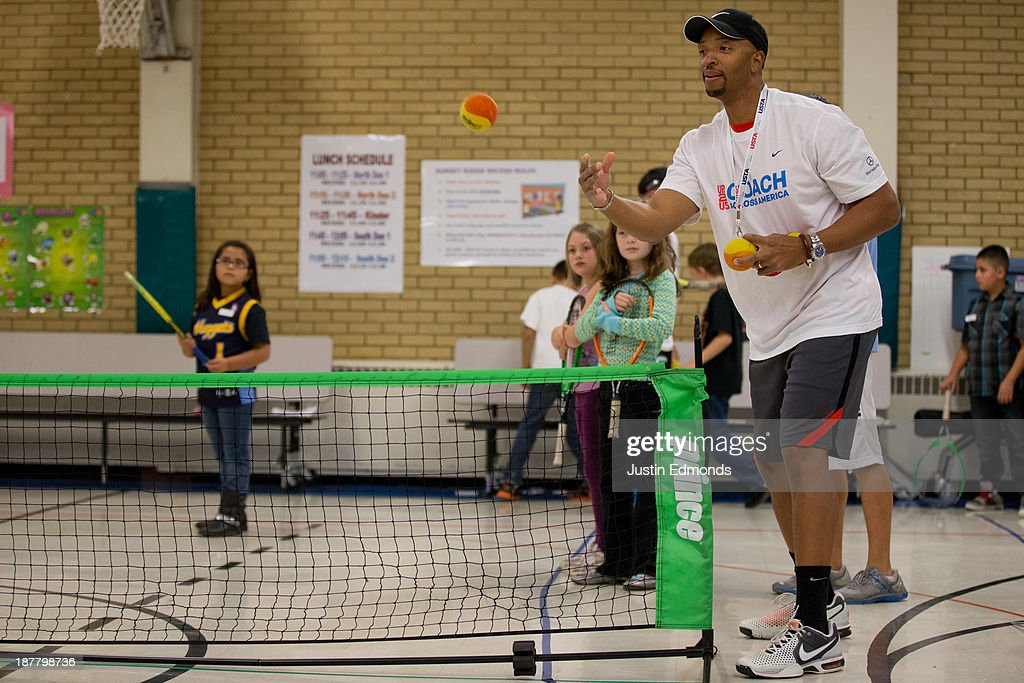 A coach tosses a ball to kids during a tennis drill during the Denver Project Launch to support Up2US's Coach Across America program at the Adams 50 USTA National Junior Tennis Learning Chapter inside Sunset Ridge Elementary School on November 12, 2013 in Westminster, Colorado.