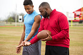 Coach giving tips to an athlete on football techniques.