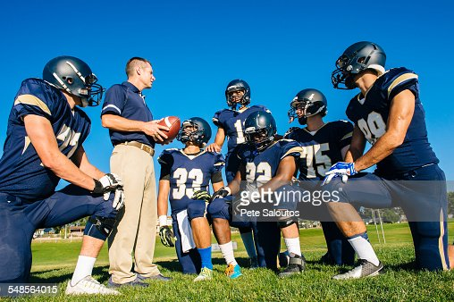 Coach training teenage and young male American football team