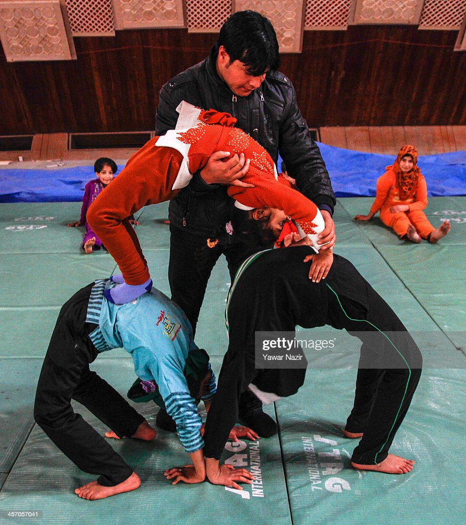 A coach trains Young Kashmiri Muslim girls during a training session inside indoor stadium on December 16, 2013 in Srinagar, the summer capital of Indian administered Kashmir, India. As the number of crimes against women has risen in the region, girls from different age groups and backgrounds have taken up martial arts and other self defence courses to thwart attackers. Many believe after the barbaric rape and murder of a para-medic student last year on this day in the Indian capital of New Delhi, women in the Muslim majority state have taken to various martial arts forms like Thang-ta, a weapon-based Indian Martial art for protection.