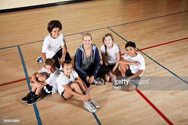 Coach with group of children in phys ed class