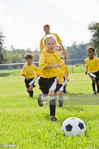 Coach with team of young children playing soccer chasing ball