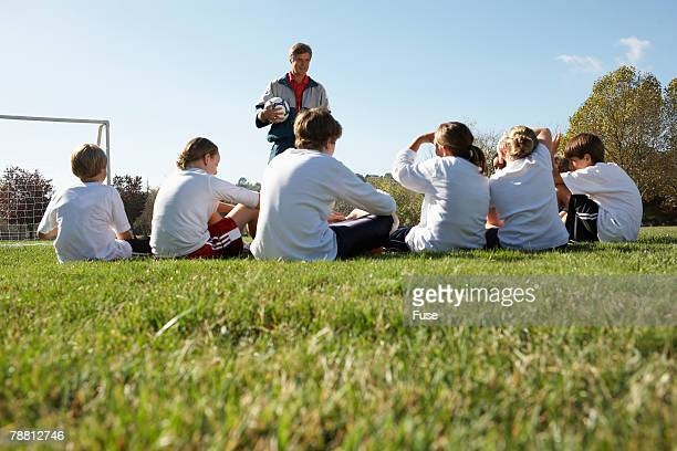 Coach with Team on Soccer Field