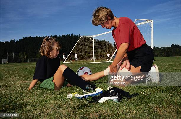 Coach Wrapping a Soccer Player's Ankle