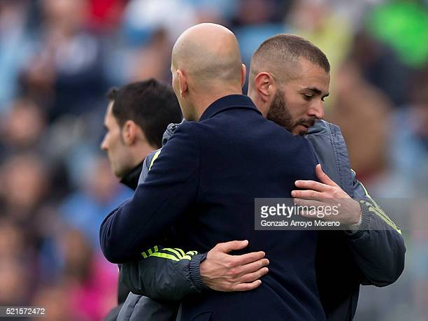 coach Zinedine Zidane of Real Madrid CF hugs his player Karim Benzema as he leaves the pithc during the La Liga match between Getafe CF and Real...