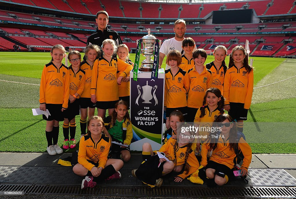 Coaches and Players of Stockfold Juniors FC pose for a team photo with the SSE Women's FA Cup during the SSE Women's FA Cup Final - Wembley Media Day at Wembley Stadium on May 6, 2016 in London, England.