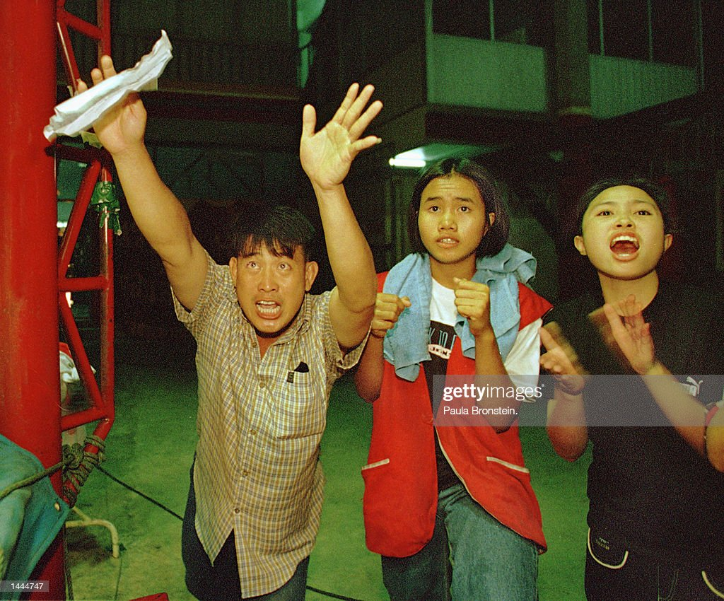 Coaches, family members, and gamblers cheer on the sidelines for their fighters during a fight at Rangsit stadium May, 2000 in Bangkok, Thailand.