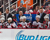 Coaches Scott Stevens Lou Lamoriello and Adam Oates of the New Jersey Devils watch the action from the bench during the annual New Year's eve game...