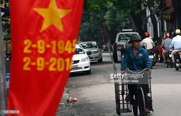 A coal brick vendor rides past a banner marking the 65th anniversary of the communist regime in downtown Hanoi on August 31 2010 The Vietnamese...