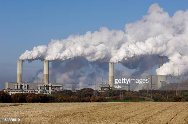 Coal burning power plant with stubble field in foreground