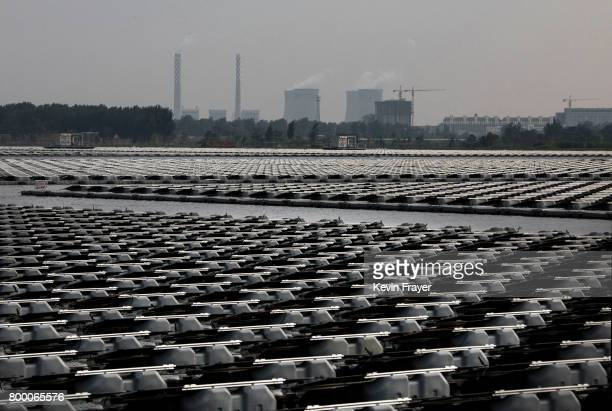 A coal fired power plant is seen beyond a section of a large floating solar farm project under construction by the Sungrow Power Supply Company on a...