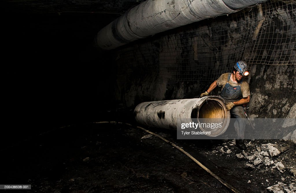 Coal miner hauling ventilation tube throuh mine, side view