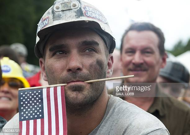 A coal miner holds an American flag in his mouth as US Republican presidential candidate and former Massachusetts Governor Mitt Romney speaks during...