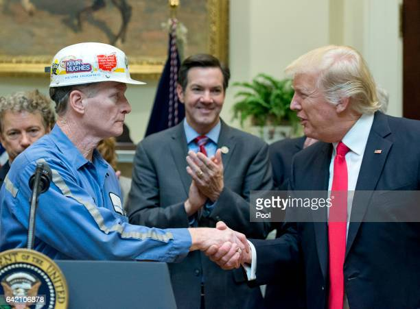 A coal miner identified as Kevin shakes hands with US President Donald Trump prior to the President signing HJ Res 38 disapproving the rule submitted...