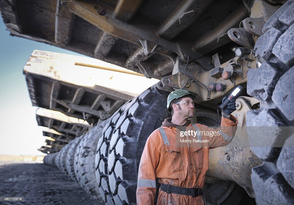 Coal miner inspects dumper truck tyre tread in surface coal mine