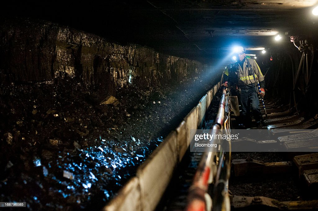 A coal miner shines his head lamp on coal transported on a conveyor belt after being sheared off the wall during longwall mining operations at the Consol Energy Bailey Mine in Wind Ridge, Pennsylvania, U.S., on Tuesday, May 14, 2013. Coal's prospects are improving after its share of U.S. power generation fell last year to 34 percent, the lowest since at least 1973, Energy Department data show. Hotter temperatures this summer that prompt American households to use more air conditioning will boost demand for coal and the railroads that ship it. Photographer: Ty Wright/Bloomberg via Getty Images