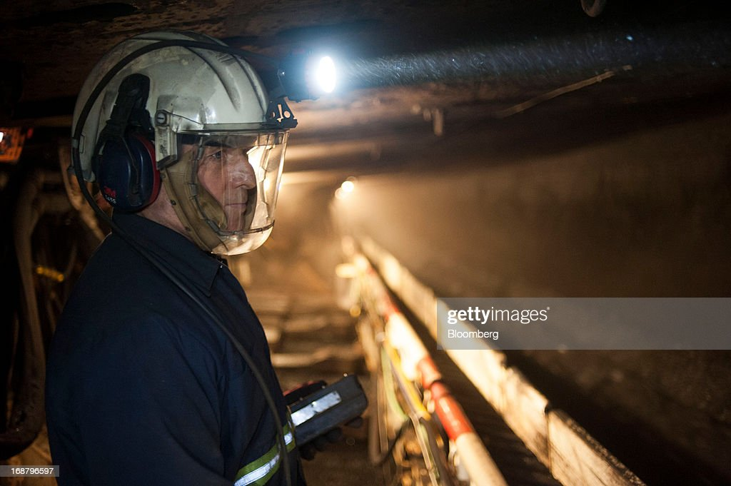 A coal miner shines his head lamp on the wall as a carbide-tipped shearer scrapes coal from the wall during longwall mining operations at the Consol Energy Bailey Mine in Wind Ridge, Pennsylvania, U.S., on Tuesday, May 14, 2013. Coal's prospects are improving after its share of U.S. power generation fell last year to 34 percent, the lowest since at least 1973, Energy Department data show. Hotter temperatures this summer that prompt American households to use more air conditioning will boost demand for coal and the railroads that ship it. Photographer: Ty Wright/Bloomberg via Getty Images