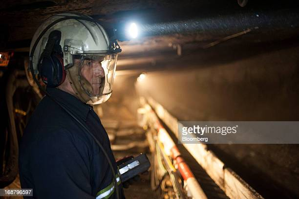 A coal miner shines his head lamp on the wall as a carbidetipped shearer scrapes coal from the wall during longwall mining operations at the Consol...