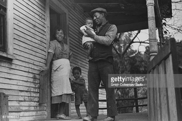 A coal miner stands on his front porch with his wife and their two children in Bertha Hill West Virginia September 1938
