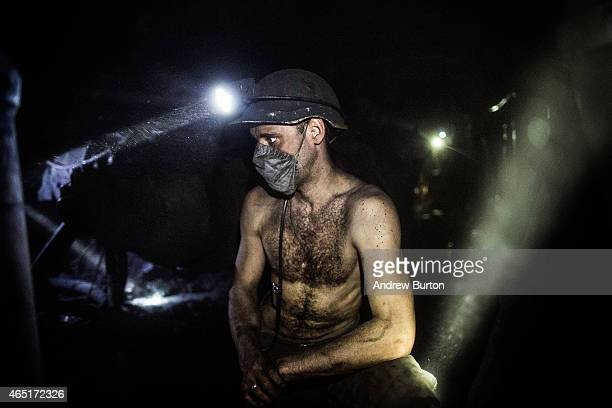 A coal miner takes a break from using a jack hammer to break up coal over 3600 feet below the surface at Scheglovka Glubokaya mine on March 3 2015 in...