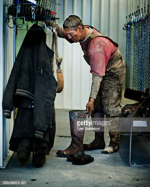 Coal miner taking off boots in locker room, side view