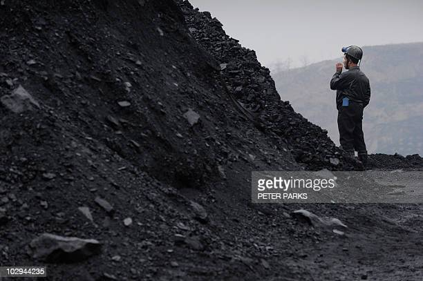 A coal miner waits for news of his colleagues near the entrance to a flooded mine shaft at the Wangjialing coal mine in northern China's Shanxi...