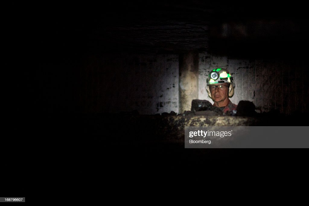A coal miner watches as a carbide-tipped shearer scrapes coal from the wall during longwall operations at the Consol Energy Bailey Mine in Wind Ridge, Pennsylvania, U.S., on Tuesday, May 14, 2013. Coal's prospects are improving after its share of U.S. power generation fell last year to 34 percent, the lowest since at least 1973, Energy Department data show. Hotter temperatures this summer that prompt American households to use more air conditioning will boost demand for coal and the railroads that ship it. Photographer: Ty Wright/Bloomberg via Getty Images
