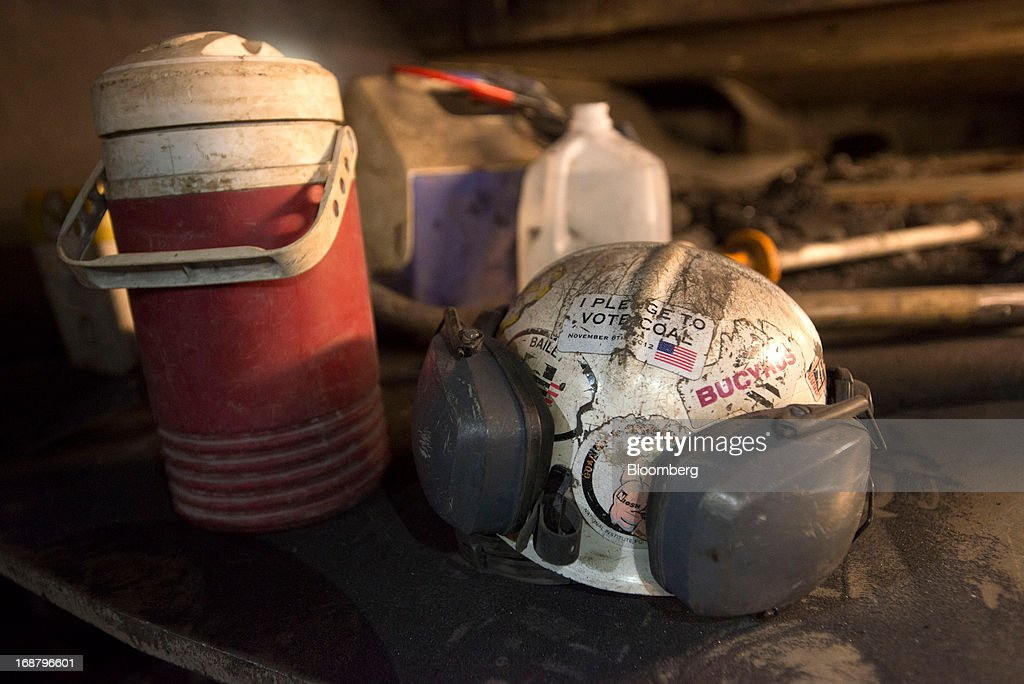 A coal miner's hard hat with a sticker that reads ' I pledge to vote coal' sits next to a lunch container at the Consol Energy Bailey Mine in Wind Ridge, Pennsylvania, U.S., on Tuesday, May 14, 2013. Coal's prospects are improving after its share of U.S. power generation fell last year to 34 percent, the lowest since at least 1973, Energy Department data show. Hotter temperatures this summer that prompt American households to use more air conditioning will boost demand for coal and the railroads that ship it. Photographer: Ty Wright/Bloomberg via Getty Images