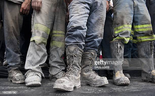 Coal miners listen as US Republican presidential candidate and former Massachusetts Governor Mitt Romney speaks during a campaign event at the...
