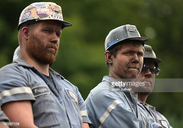 Coal miners look on as Republican presidential candidate and former Massachusetts Governor Mitt Romney speaks during a campaign rally at American...