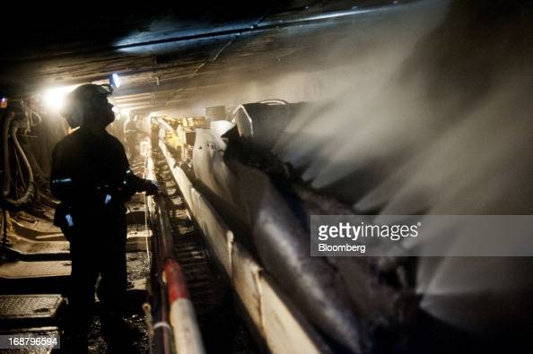 Coal miners shine their head lamps on the wall as a carbidetipped shearer scrapes coal from the wall during longwall mining operations at the Consol...
