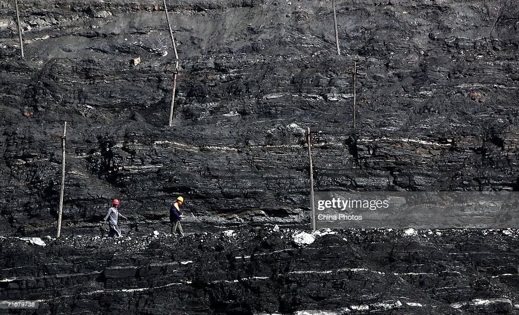 Coal miners walk on coal seams in an open pit coal mine on August 19, 2006 in Chifeng of Inner Mongolia Autonomous Region, China. Pingzhuang Coal Groups Company, including six open pit coal mines, produces 10 million tons per year. Reportedly, in the first four months of this year, China's coal consumption rose by 13.8 percent over the same period of last year, and coal price is expected to go up steadily with the factors of environment, safety and resources included in the cost of coal production.
