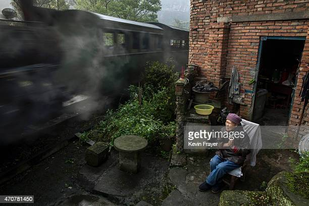 A coal powered steam engine carries local passengers as villager Peng 80 years looks on from in front of her house on March 29 2015 in the village of...