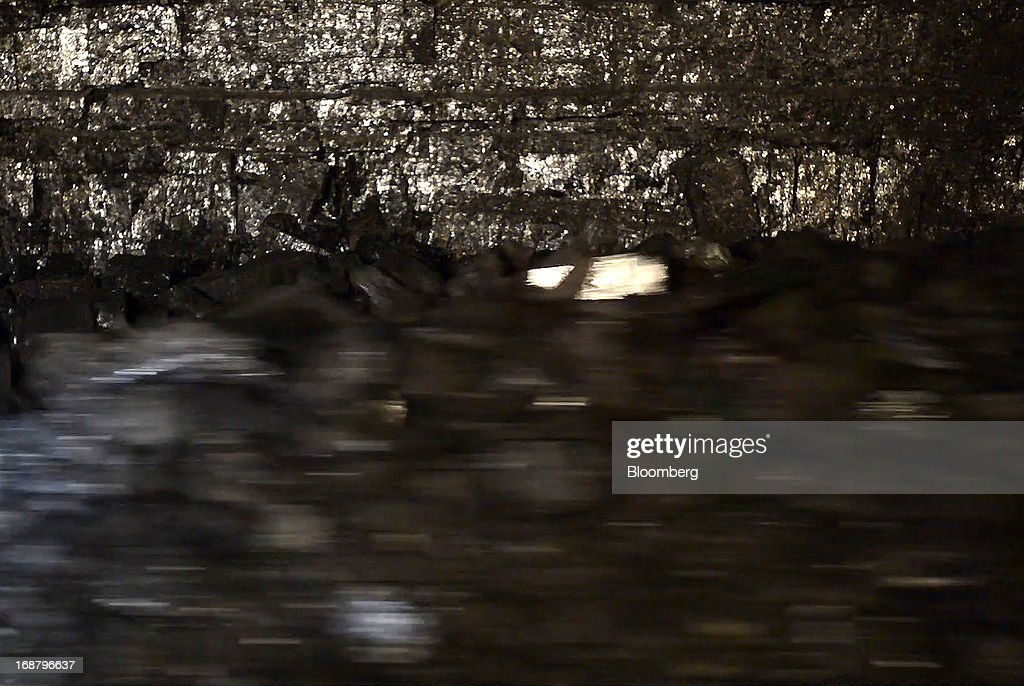 Coal runs along a conveyor belt after being scraped off the wall by a shearer during longwall mining operations at the Consol Energy Bailey Mine in Wind Ridge, Pennsylvania, U.S., on Tuesday, May 14, 2013. Coal's prospects are improving after its share of U.S. power generation fell last year to 34 percent, the lowest since at least 1973, Energy Department data show. Hotter temperatures this summer that prompt American households to use more air conditioning will boost demand for coal and the railroads that ship it. Photographer: Ty Wright/Bloomberg via Getty Images