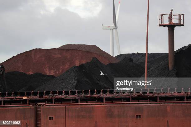 Coal sits in a storage yard as a wind turbine operates beyond at the Port of Hamburg in Hamburg Germany on Wednesday Sept 20 2017 Germany's...