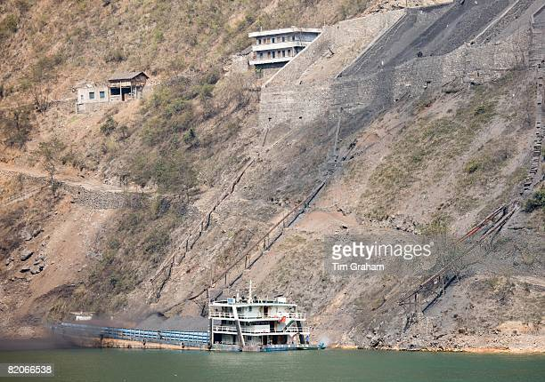 Coal slides down hillside to fill freight ship in Three Gorges area Yangtze River China