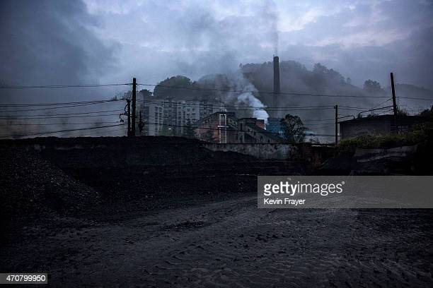 Coal to be used by coal powered steam engines is seen backdropped by a coal fired power plant on March 27 2015 at a station near the town of Shixi...
