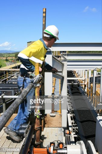 Coal Worker in safety uniform looking at a conveyor belt